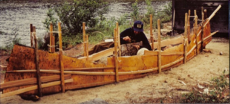 Basil Smith uses split spruce root to sew the seams of a new birchbark canoe . The birchbark  has been laid out on a sand building bed and staked into the shape of the canoe ; from '' Building an Algonquin Birchbark Canoe '' ; photo Henri Vaillancourt , Maniwaki , Quebec 1980