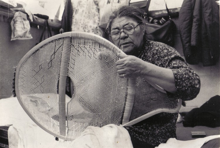 Sarah Bosum of Mistassini lacing the midsection of a man's beavertail snowshoe with caribou skin. The loose end of the string is held in the mouth to maintain tension on the weave , Lac Capichigamau , Quebec 1985; photo Henri Vaillancourt