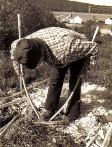Moise Flamand pulling a square-toe snowshoe frame into shape ; the frame has been entirely pre-bent over the knee prior to the final bending ; Manouane, Quebec 1979 ; from ''Making the Attikamek Snowshoe'' , photo Henri Vaillancourt