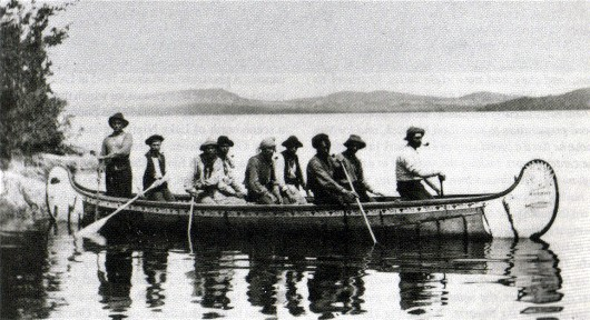 Elaborately  decorated fur-trade birchbark canoe on Lake Chibougamau in Quebec named the ROBROY ; the more highly finished canoes were often decorated with complex patterns such as the floral motif bordering the gunnels in this canoe, and given named after the fashion of European boats.