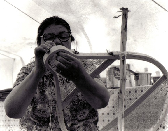 Sarah Bosum lacing the tail of a  beavertail snowshoe with caribou  skin string ; caribou skin is considered superior to most other skins because its fine grain makes it very durable. Mistassini, Quebec, 1977 ; photo from the video''Beavertail Snowshoes'' , Henri Vaillancourt