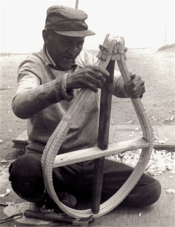 Mathieu Mestenapeo of La Romaine, Quebec examining a newly bent pair of beavertail snowshoes . These frames are bent with an exceptionally  tight rounded tail....just one of the many variant patterns of beavertail snowshoes in the Quebec- Labrador area  ; photo 1978, Henri Vaillancourt