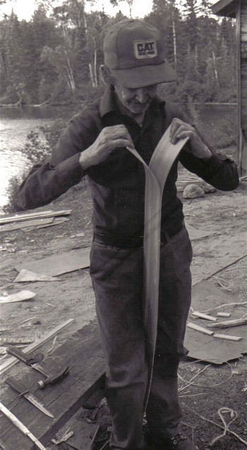 Basil splitting cedar for the planking of a birchbark canoe . Birchbark canoes often have planking a mere 1/16 '' in thickness ; from  ''Building an Algonquin Birchbark Canoe '' ; photo Henri Vaillancourt ; Maniwaki Quebec 1980